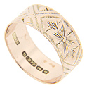 Engraved crossing shapes alternate with floral patterning on the surface of this 14K rose gold antique wedding band