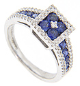 A cluster of four round blue sapphires is set in the head of this 14K white gold modern ring