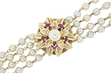 A 14K yellow gold blooming floral design decorates the middle of this vintage pearl bracelet