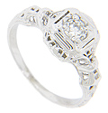 Ornate designs done in relief decorate the shoulders of this 14K white gold antique engagement ring