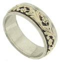A yellow gold floral pattern crafted in relief, ornaments the center of this 14K gold estate men's wedding ring