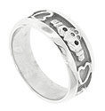 A handsome carved 14K white gold claddagh design decorates the center of this modern mens wedding band