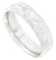 A wave of richly engraved organic figures cover the face of this 14K white gold mens wedding band