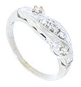 A flowing organic leaf set with diamonds drapes across the face of this 14K white gold wedding band