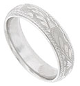 Intricate organic engraving covers the rough carved surface of this 14K white gold mens wedding ring