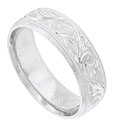 The rough etched surface of this 14K white gold mens wedding band is decorated with a deeply engraved pattern of leaves and twisting vines