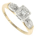 This vintage 14K bi-color engagement ring features a white gold floral embellished face and shoulders
