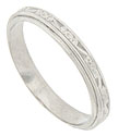 This elegant antique style wedding band is crafted of platinum and engraved with a repeating pattern of abstract organics