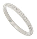 Abstract organic engraving covers the face of this antique style platinum wedding band
