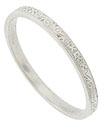 Delicate organic engraving adorns the surface of this antique style platinum wedding band