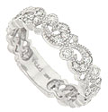A tumble of crescent shaped leaves and miniature blossoms dance across this 14K white gold floral wedding band