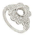 This floral inspired platinum mounting is covered in twisting ribbons of fine faceted diamonds that finish in a rounded braid on either shoulder