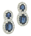 A pair of oval cut sapphires surrounded by round faceted diamonds adorn the surface of these elegant 14K white gold earrings