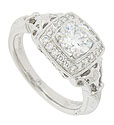This elegant 14K white gold engagement ring features a bold frame of round faceted diamonds
