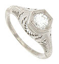 Bold organic filigree and rich engraving adorn the sides and shoulders of this antique style engagement ring