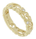 Delicate blooming vines wind around the face of this 14K yellow gold floral wedding band