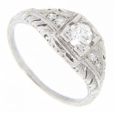 Curving ornate designs frame pairs of diamonds on the shoulders of this platinum antique style engagement ring