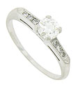 A sparkling F color, Vs1 clarity round faceted diamond is the star of this vintage engagement ring