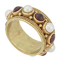 Luminous pearls and cabochon garnets are bezel set around the entire circumference of this 14K yellow gold vintage ring