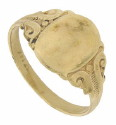 Wide organic engraved shoulders frame the smooth oval face of this 14K yellow gold antique ring