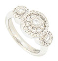 Large faceted diamonds surrounded by rings of additional diamonds are set into a floral pattern on the face of this antique style engagement ring