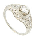 A luminous .41 carat, I color, Si1 clarity round diamond is set into the face of this platinum antique style engagement ring