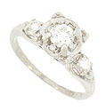 A brilliant .40 carat, F color, Si1 clarity round diamond rests in the center of this floral inspired engagement ring