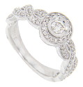Intertwining lines of white gold and diamonds run down the shoulders of this 14K white gold antique style engagement ring