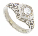 This antique style 18K white gold engagement ring features a branching leaf design on the sides