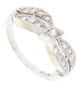 A single round diamond set in a marquis shape is flanked by curving double rows of diamonds on either side