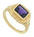 A deep purple rectangular cut amethyst is set into the face of this 14K yellow gold antique ring