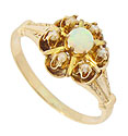 This phenomenal 10K yellow gold antique ring features a floral design and is set with a glowing cabochon opal