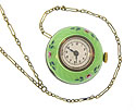 This round vintage watch is covered in green enamel dotted with pink roses and green leaves