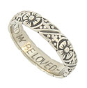 A bold engraved floral pattern covers the surface of this 14K white gold estate wedding band