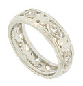 Distinctive organic cutouts set with fine faceted diamonds dance across the face of this platinum wedding band
