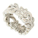 Full figured blooms and curling leaves twist across the face of this 14K white gold estate wedding band