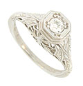 A dazzling .16 carat round cut diamond is set into the face of this antique style engagement ring