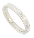 A stippled and engraved floral design covers the surface of this 14k white gold wedding band