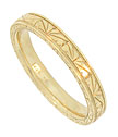 This sparkling 14K yellow gold wedding band is embellished with deeply engraved abstract organic designs