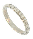 This romantic antique style wedding band is fashioned of platinum and adorned with a string of deeply engraved blossoms