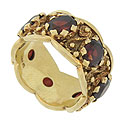 This sparkling 14K yellow gold scalloped wedding band is set with seven oval faceted garnets