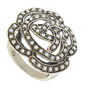 Swirling figures of sterling silver form the face of a rose on this distinctive antique style ring
