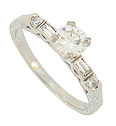 A dazzling .48 carat, H color, I1 clarity round cut diamond floats above the face of this spectacular engagement ring
