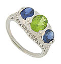 This fantastic platinum engagement ring features a pair of oval cut sapphires framing a glowing oval cut peridot