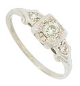 A fiery .24 carat, H color, Si1 clarity round diamond adorns the face of this 14K white gold vintage engagement ring