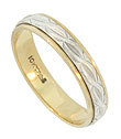 This radiant 10K bi-color wedding band is crafted with a ribbon of white gold engraved organic figurals pressed into a brightly polished yellow gold band