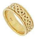 A bold Celtic inspired decoration adorns the face of this 14K yellow gold estate wedding band