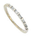 A string of seven brilliant diamond baguettes are set into the face of this 14K white gold estate wedding band