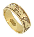 This extraordinary 18K yellow gold antique wedding band is engraved with a pattern of large abstract leaves