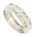 Large curling leaves and full figured blooms dance across the face of this 14K white gold Edwardian wedding band